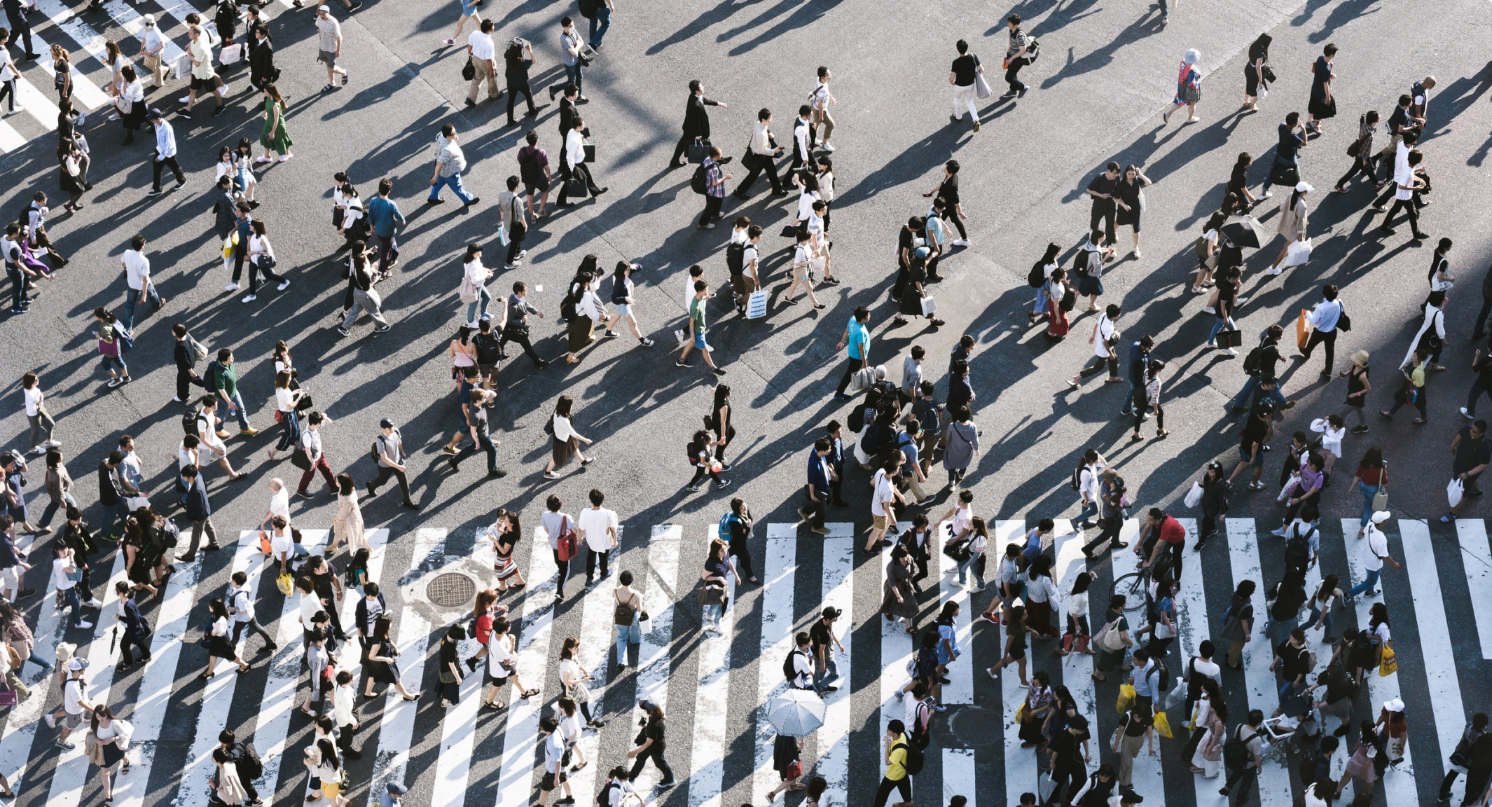 A top down image of a large crowd crossing a street in many directions.